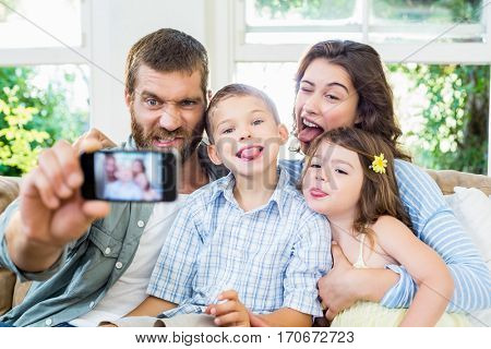 Happy family taking a selfie on mobile phone in living room