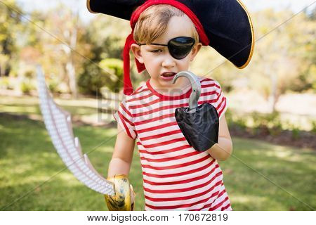 Little boy pretending to be a pirate in the park poster