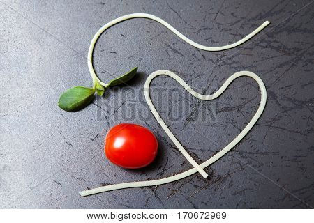 heart shape of spaghetti and grape tomatoes on Black pan