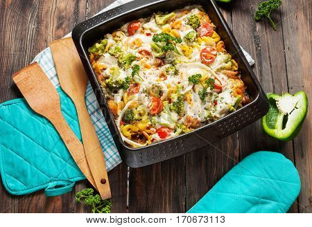 Baked pasta with broccoli and cheesy tomato sauce on wood background.