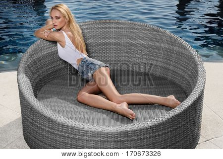 Beautiful blond woman in white swimsuit and jeans shorts lying on lounger by the pool during summer day