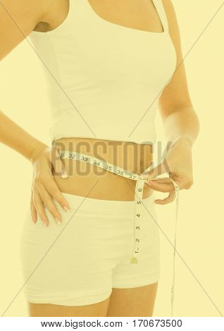 Mid section of woman measuring waste with measuring tape