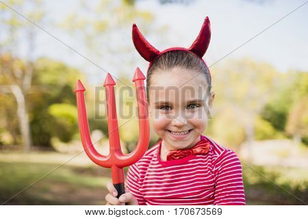 Adorable girl pretending to be a devil in the park