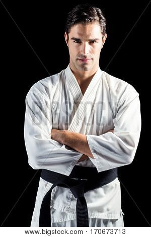 Portrait of fighter standing on black background with arms crossed