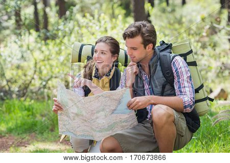 Couple crouching and planning with map during hiking