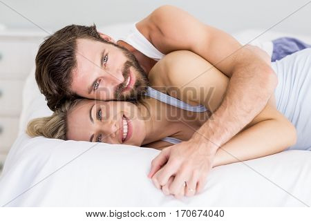 Portrait of romantic couple embracing on bed in bedroom