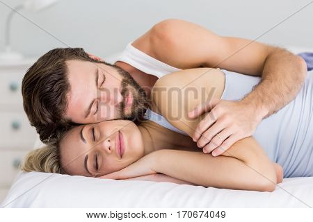 Young couple sleeping on bed in bedroom