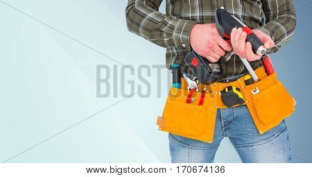 Mid section of handyman holding drill machine and plank against blue background