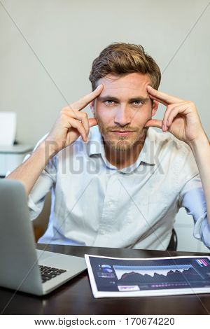 Portrait of frustrated businessman sitting by table in office