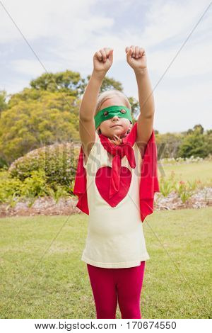 Little girl pretending pretending to fly with superhero costume in the park