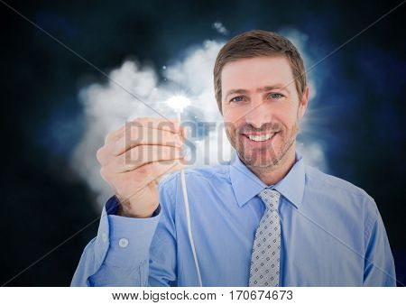 Portrait of businessman holding cable with flare against digitally generated cloud background