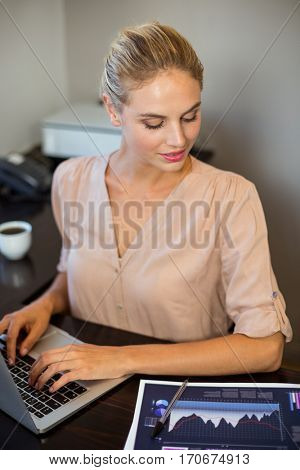 High angle view of businesswoman looking into document in office