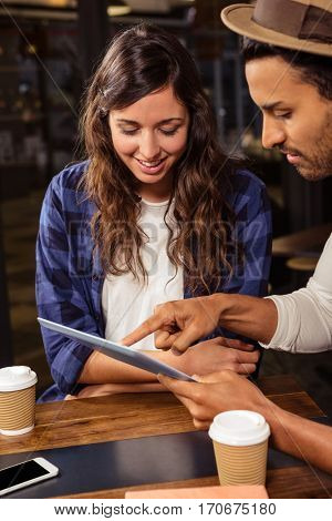 Couple using a tablet in a coffee shop