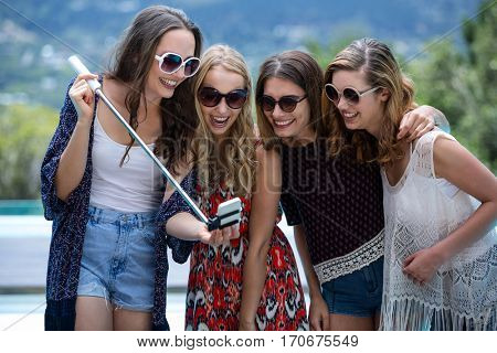 Beautiful women looking at mobile phone and smiling near pool
