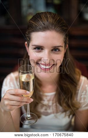 High angle portrait of happy woman holding champagne flute at restaurant