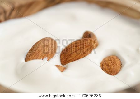 macro shot of homemade yogurt with almonds in wood bowl on wooden table, shallow focus