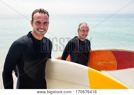 Portrait of happy father and son in wetsuit holding a surfboard on the beach