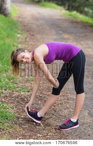 Portrait of happpy young woman touching shoe while exercising in forest