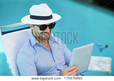Smart man relaxing on sun lounger and using a digital tablet near pool