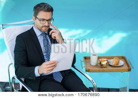 Smart man relaxing on sunlounger and reading document near pool