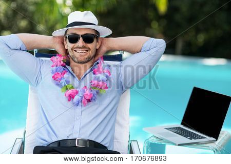 Smart man wearing garland while relaxing in sun lounger near pool