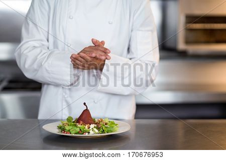 Midsection of chef grinding pepper on salad in a commercial kitchen