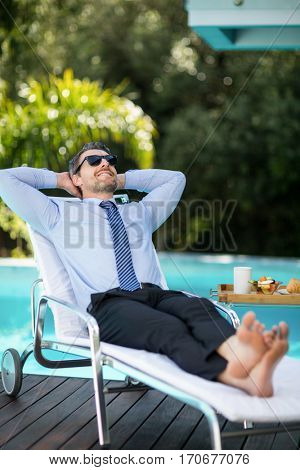 Smart man relaxing on sun lounger near pool