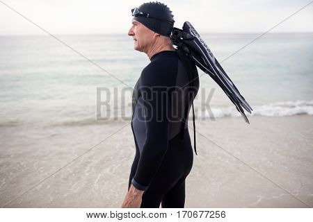 Senior man with flipper standing on beach on a sunny day