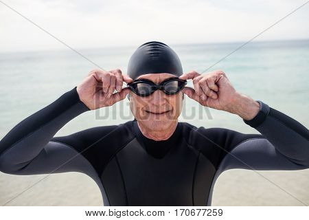 Portrait of senior man in wetsuit and swimming goggles standing on beach on a sunny day
