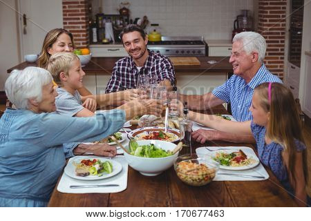 Smiling multi generation family toasting drink while celebrating thanksgiving at home