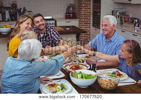 Smiling multi generation family toasting white wine while celebrating thanksgiving at home