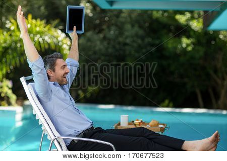 Excited man relaxing on sun lounger and holding a digital tablet near the pool