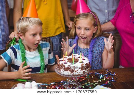 Shocked siblings with birthday cake at home