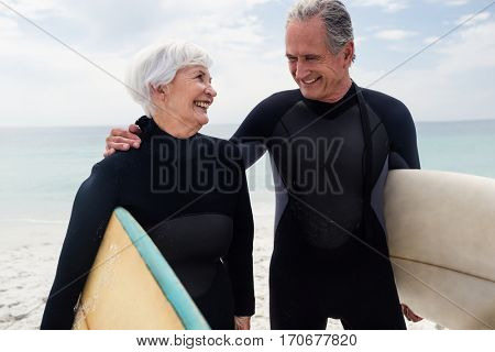 Happy senior couple in wetsuit holding surfboard on beach on a sunny day