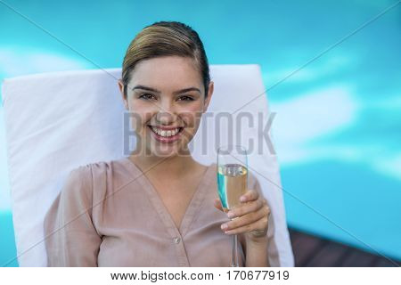Businesswoman relaxing on sunlounger and holding champagne flute near pool