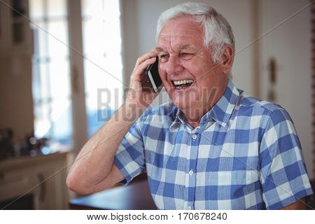 Cheerful senior man talking on mobile phone at home