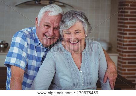 Confident happy senior couple in kitchen