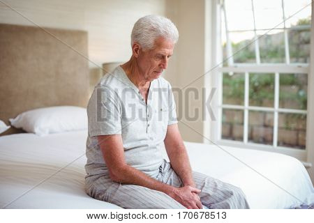 Worried senior man looking down while sitting on bed in room