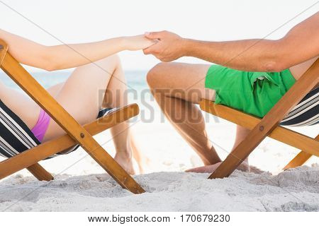 Couple sitting on deck chair holding hands on the beach