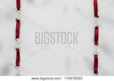 Fashionable beautiful background red satin ribbon inserted in white satin fabric with space for your creativity. View from above.