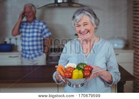 Senior woman holding colander with husband in background