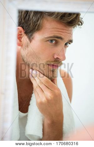 Reflection of young man in mirror checking his stubble in bathroom