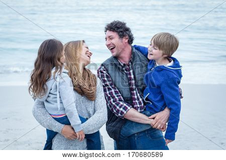 Cheerful parents enjoying with children at sea shore