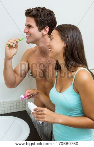 Close-up of smiling couple brushing their teeth bathroom