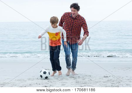 Full length of father and son playing soccer at beach