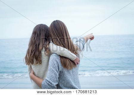 Rear view of mother pointing while embracing daughter at sea shore