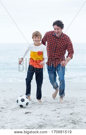 Full length of cheerful father and son playing at sea shore