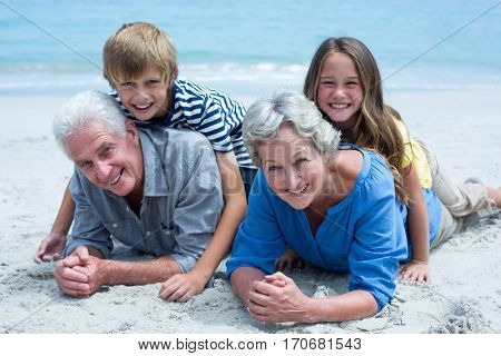 Portrait of children lying on grandparents at sea shore