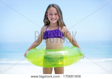 Portrait of cheerful girl with inflatable ring standing at sea shore