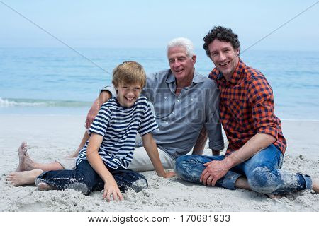 Portrait of multi-generation family smiling while relaxing at sea shore